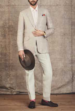 Jacket by Huntsman; Shirt by Emma Willis; Pocket Square by Rubinacci; Hat by Lock & Co; Trousers by Edward Sexton; Socks by The London Sock Company; Loafers by Cheaney; Watch is a Rolex 'Padellone' ref 8171, circa 1951 with two-tone dial in 18k yellow gold.
