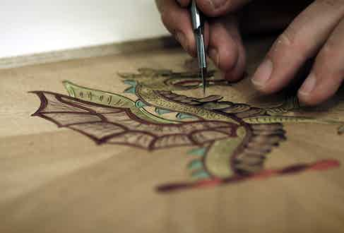 Hand-drawing the designs onto each board entails an intensive process.