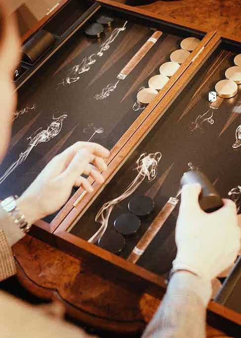 Alexandra Llewellyn's Black and Brown Wood Cigar Backgammon Set opens to reveal swirling smoke and cigars amongst triangles of printed tobacco leaves.