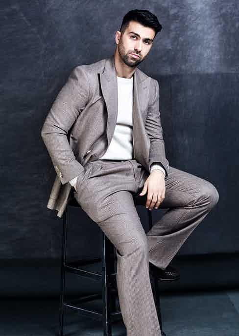 The actor David Mumeni dresses down pale grey pinstripe suit by using a white crew neck. It's casual, but framed within the smart lines of the suit.