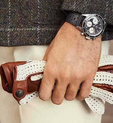 Details of Tag Heuer's 1966 chronograph featuring Omega SRL's ivory crochet and brown leather driving gloves.