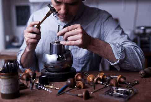 Smith at work engraving a signet ring.