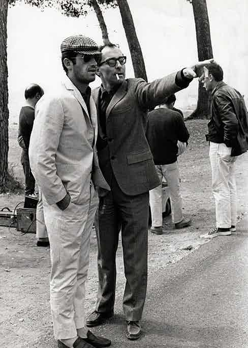 Belmondo off camera, taking instructions from French cinema's greatest director, Jean Luc Godard.