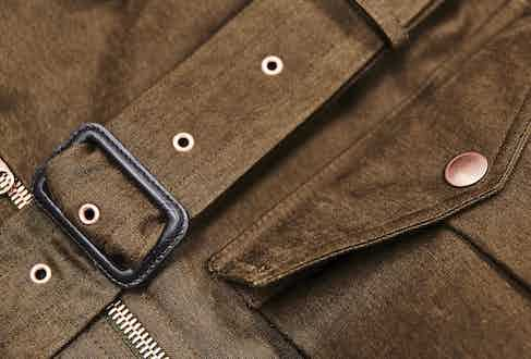 D-Ring belt buckle and copper rivets reinforce the jacket.
