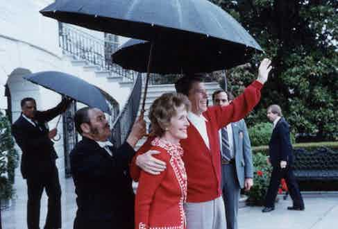 US President Ronald Reagan under an umbrella with First Lady Nancy Reagan after leaving George Washington Hospital, Washington, DC (Photo by Ronald Reagan Library/Getty Images).