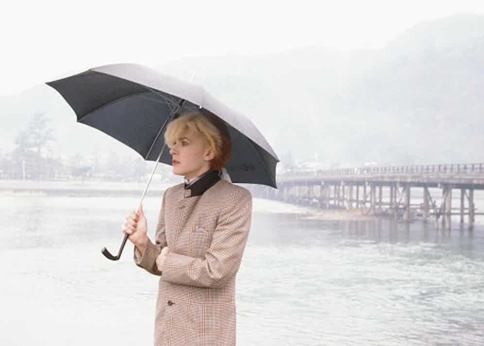 David Sylvian an English singer-songwriter standing with umbrella at the riverside in rainy Arashiyama Kyoto, Kyoto, February 1981 (Photo by Koh Hasebe/Shinko Music/Getty Images).