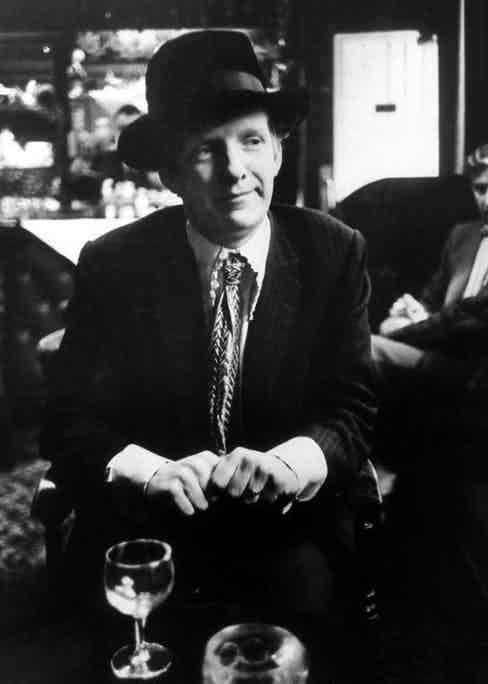Christopher Gibbs sitting with a drink, wearing a white lace shirt.