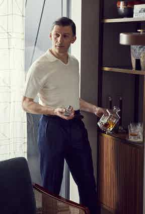 White linen cotton mix polo shirt, Mc Lauren; Navy flannel Hollywood top pleated wool trousers, Edward Sexton; Belt, Stylists own; Brown socks, The London Sock Company.