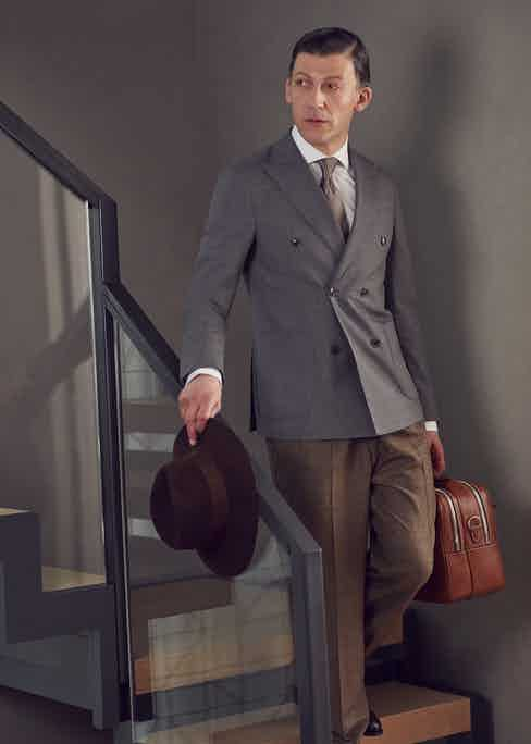 Grey wool Erik double-breasted jacket, Oscar Jacobson; Blue and white stripe business shirt, Gieves and Hawkes; Light and dark brown diamonds and orange spot silk tie, Edward Sexton; Sage Manny pleated flannel trouser, Rubinacci; Dark antique oak Berkeley leather oxfords, Edward Green; Brown beaver felt lock & co X The Rake 'pall mall' fedora, Lock & Co Hatters.