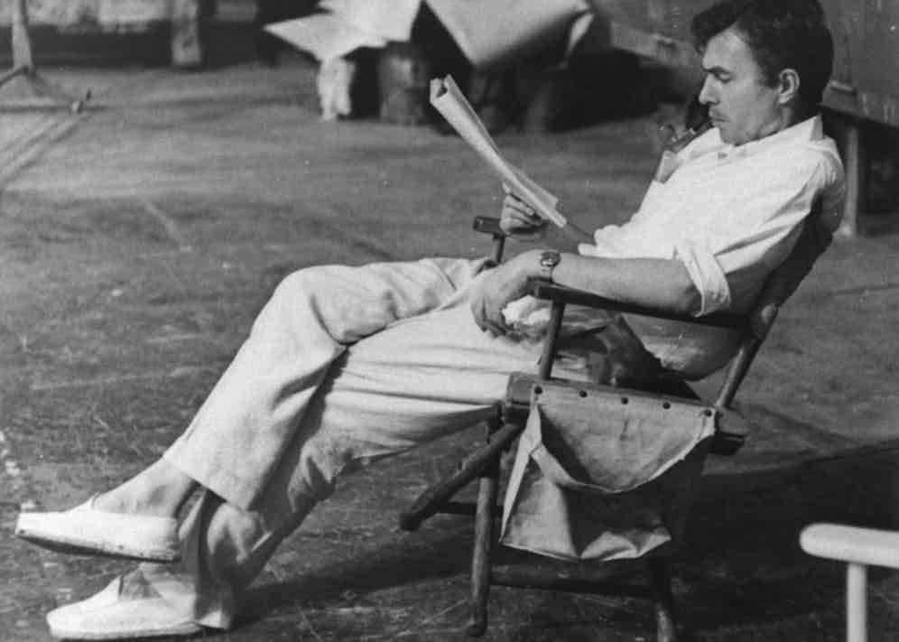 Actor James Mason smoking a pipe while reading a script on the set of Julius Caesar in 1952.