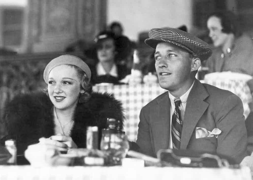 The entertainer Bing Crosby with a guest at the racetrack.