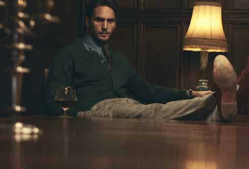 Green cashmere cardigan, Anderson & Sheppard at The Rake; sky blue cotton tab collar shirt, Edward Sexton at The Rake; burgundy silk medallion print tie, Drake's at The Rake; grey wool Blake check Aleks trousers, Kit Blake at The Rake; passport-red Redcliff Date watch with Fears blue leather strap, Fears at The Rake.