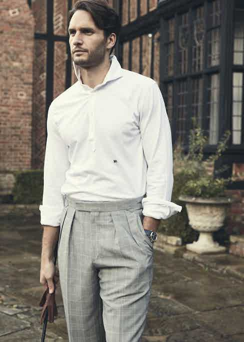 White cotton long sleeve polo, Kit Blake at the Rake; grey wool Blake check Aleks trousers, Kit Blake at The Rake; blue Redcliff Continental watch with leather strap, Fears.