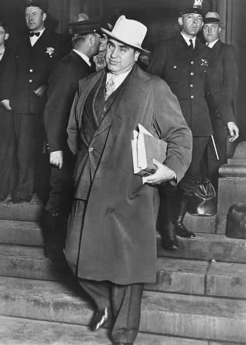 Al Capone winks at photographers as he leaves Chicago's federal courthouse, 1931. The notorious Chicago gangster was on trial for tax evasion.