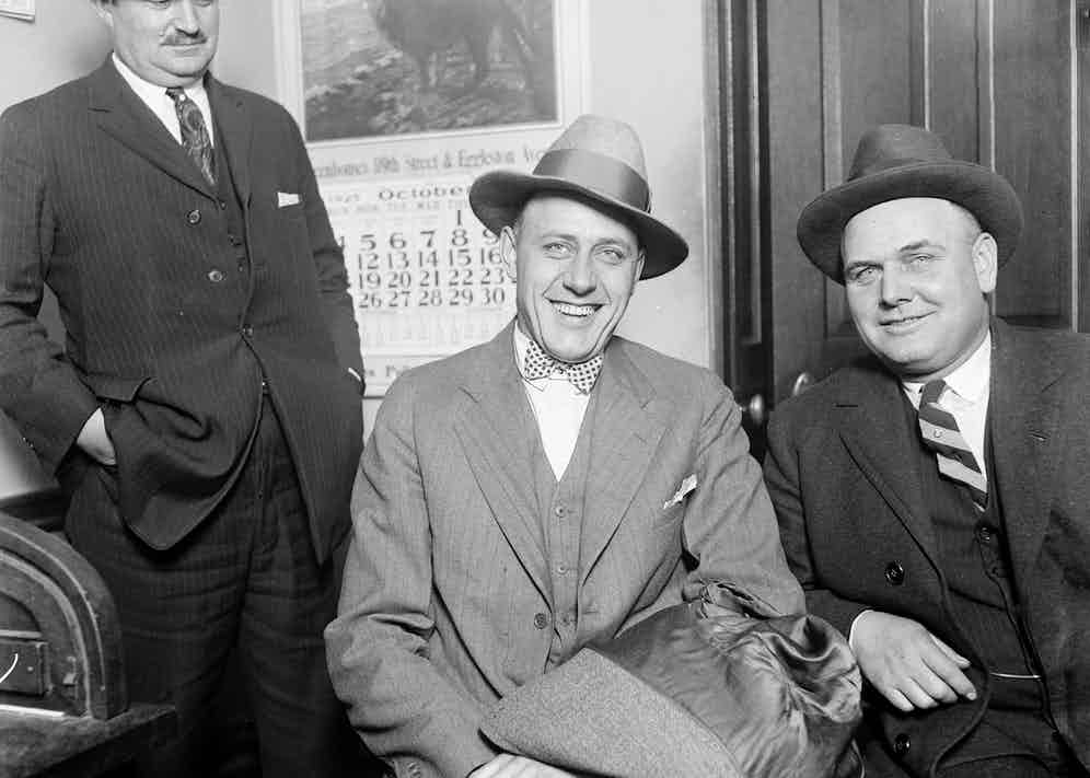 """UNITED STATES - CIRCA 1925: Portrait of a smiling Edward """"Spike"""" O'Donnell (center) sitting with an unidentified man in a room in Chicago, Illinois, 1925. O'Donnell was a South Side gangster active during the Beer Wars of early Prohibition. (Photo by Chicago Sun-Times/Chicago Daily News collection/Chicago History Museum/Getty Images)"""