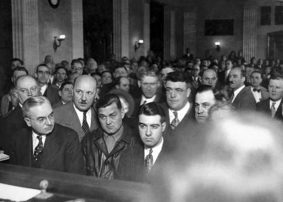 """1925: George """"Bugs"""" Moran (in leather jacket), leader of Chicago's North Side gang, shown in court, Chicago, ca.1920s. Moran escaped, but was the intended target of the St. Valentine's Day killings ordered by Al Capone. (Photo by Chicago History Museum/Getty Images)"""