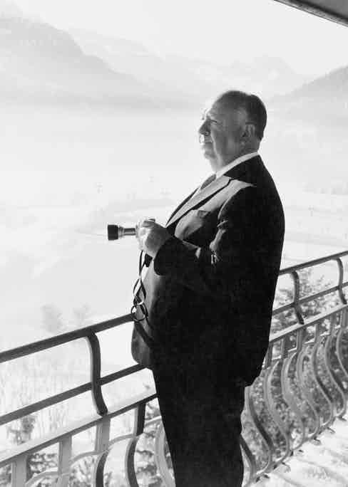 Alfred Hitchcock admiring the view from his balcony during a holiday in St Moritz, Switzerland, circa 1955. (Photo by Pictorial Parade/Archive Photos/Getty Images)