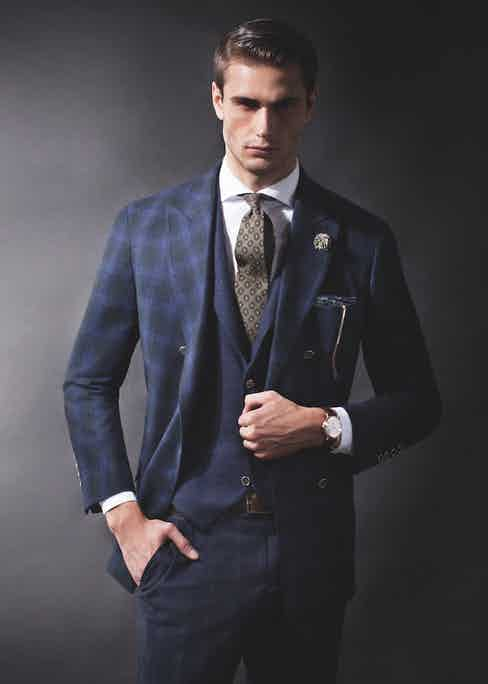 Blue and green tartan wool-cashmere double-breasted sport coat, blue cashmere single-breasted vest, white spread-collar cotton shirt, blue and black Prince of Wales-check trousers, brown leather belt, and blue and green geometric-pattern silk pocket square, all Brunello Cucinelli; Classique ref. 5277BR timepiece in 18k-rose-gold case and brown alligator-leather strap, Brequet. Green, maroon and yellow floral wool tie, Polo Ralph Lauren; blue and white cotton floral boutonniere, Q Menswear; gold vintage aviators (all property of The Rake).