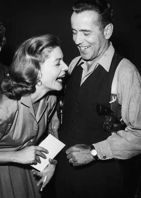 Lauren Bacall and Humphrey Bogart share a joke on the set of the Producers' Showcase television broadcast in 1955.