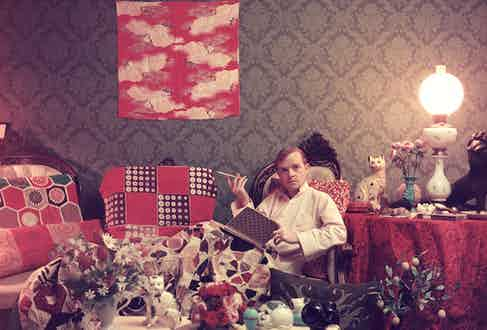 Author Truman Capote (1924 - 1984) relaxes with a book and a cigarette in his cluttered apartment, Brooklyn Heights, New York. Original Publication: A Wonderful Time - Slim Aarons   (Photo by Slim Aarons/Getty Images)