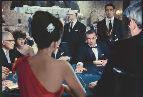 James Bond (SEAN CONNERY) faces Sylvia Trench (EUNICE GAYSON) across the Chemin de Fer table at the 'Le Cercle' casino. Bond deals a card to Sylvia in his first scene on the silver screen. (From Taschen Book, page 24) and (Courtesy of Eon Productions).