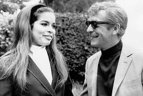 British actor Michael Caine, smiling, walking in a park with her girlfriend, Nicaraguan model Bianca De Macias. Turin (Italy), August 1968. (Photo courtesy of Getty)
