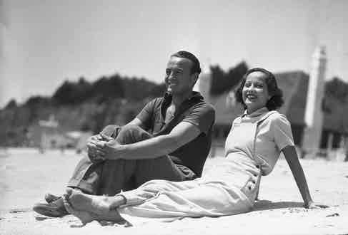 Merle Oberon, British screen favorite, is pictured above with David Niven, ex-lieutenant in the Scottish Highland Infantry, and son of the late Lady Comyn-Platt, at Santa Monica Beach, California. (Photo courtesy of Getty)