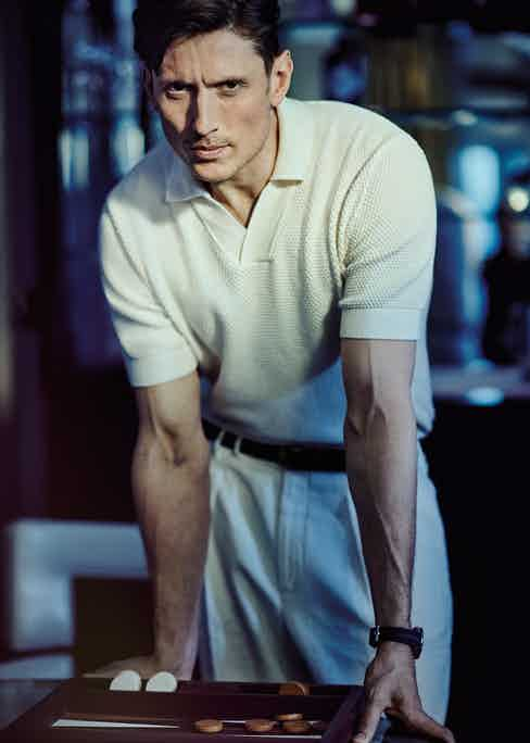 Cream knitted Merino open collar shirt, Frescobol Carioca; white linen double pleated trousers, Brunello Cucinelli; belt, stylist's own. Seamaster Diver 300M James Bond 50th Anniversary Limited Edition, Omega.