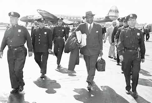 Paul Robeson is escorted by police as he arrives at LaGuardia Field. (Photo by Art Edger/NY Daily News Archive via Getty Images)