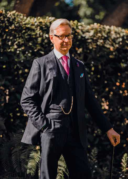 Bespoke pinstripe three-piece navy suit, Anderson & Sheppard; pink party balloon tie and boutonnière, Charvet; white bespoke shirt, Anto of Beverly Hills; pocket-handkerchief, Penrose; eyewear, Prada; antique chain attached to rose-gold pocket-watch, Patek Philippe.