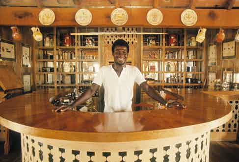 Basil Charles behind the bar at Basil's on Mustique, 1972. (Photo by Lichfield/Getty Images).