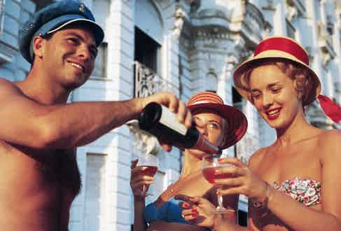 Swimsuited revellers enjoy a glass of wine outside the Carlton Hotel, Cannes.  (Photo by Slim Aarons/Getty Images)