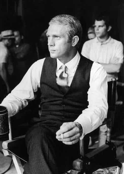 A behind the scenes shot of McQueen taking a break in between takes on the set of The Thomas Crown Affair.