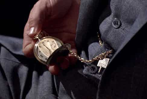 Crown checks his gold Patek Philippe pocket watch.
