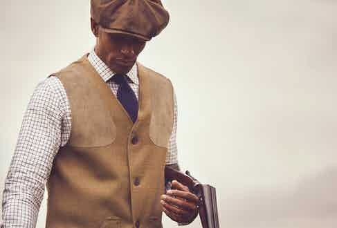 Bembridge tech tweed shooting vest and breeks, Dalby Loden bakerboy cap and Pentire crossknit alpaca shooting sock with light blue garters, all Purdey & Sons; brown and navy Oxford check cotton shirt and navy cashmere tie, Emma Willis; dark brown calfskin Husaren boots, Ludwig Reiter at TheRake.com.