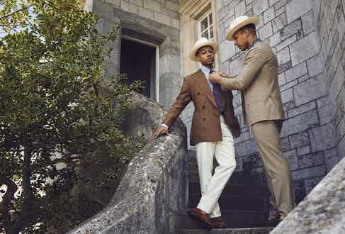 Solomon: Brown linen double- breasted jacket, Rubinacci at The Rake; blue linen buttondown shirt, 100 Hands at The Rake; burgundy Paisley silk Madder tie, Budd Shirtmakers; cream wool trousers, G. Inglese at The Rake; classic Panama Hat, Lock & Co; tan Polo suede Gabriel tassel loafer, George Cleverley. Kidane: Tan wool double-breasted suit, Gaiola at The Rake; indigo block print short-sleeve shirt, Kevin Seah; wide brim Panama hat, Lock & Co; brown mink suede Islington shoe, Edward Green.