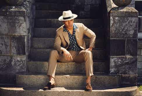 Tan wool double-breasted suit, Gaiola at The Rake; indigo block print shortsleeve shirt, Kevin Seah; wide brim Panama hat, Lock & Co; brown mink suede Islington shoe, Edward Green.