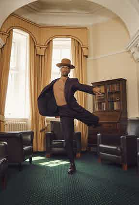 Solomon: Plum wool suit with black stripes and high-waisted trousers, XXX Ermenegildo Zegna; camel cotton T-shirt, Sunspel; Cotswold brown grain calf leather Bryan full brogue derby boot, George Cleverley. Hat and earrings, Solomon's own.