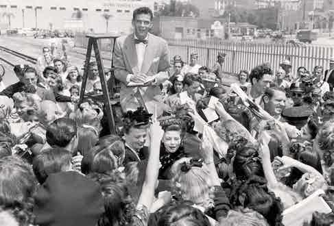 Sinatra stands on a ladder as he signs autographs for a crowd of fans in Los Angeles, 1943 (Photo by Gene Lester/Getty Images)