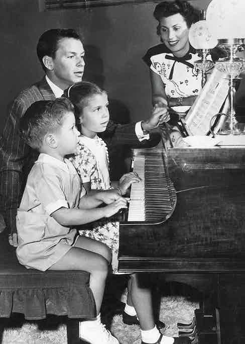 Sitting at the piano with his first wife, Nancy Barbato, and their children, Nancy and Frank Jr. (Photo by Hulton Archive/Getty Images)