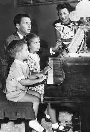 Frank Sinatra sits at the piano with his first wife, Nancy Barbato, and their children, Nancy and Frank Jr. (Photo by Hulton Archive/Getty Images)