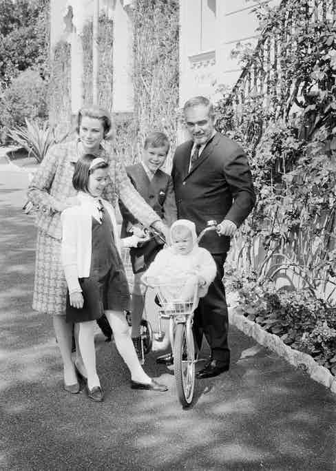 Posing in the garden of their palace, Prince Rainier and Princess Grace of Monaco, who will mark their 10th wedding anniversary April 18th, are shown with their children: Princess Stephanie, 14 months; Princess Caroline, 9; and Prince Albert, 8. (Image by © Bettmann/CORBIS)
