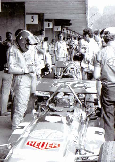 Siffert getting ready for a race, with Heuer logos on his suit and car