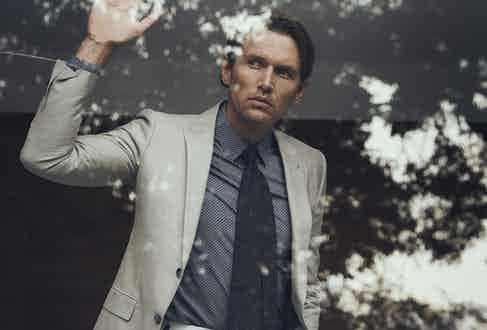 Oatmeal linen blazer, Zegna; navy and brown spot cotton shirt, Cifonelli; brown wool tie, Lardini; off-white cotton slim Aleks trousers, Kit Blake at The Rake