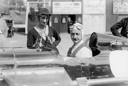 Sir Henry Birkin sits in his Blower Bentley and talks with Mrs Elsie Wisdom. Photo by Barratts/PA Images via Getty Images.