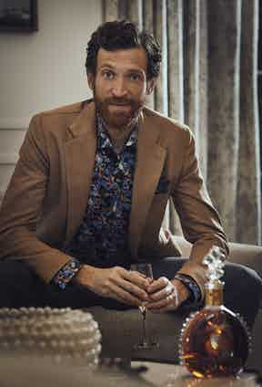 Camel wool jacket, De Petrillo; Retrofuture print shirt, Eton; Navy and brown cotton pocket square, Anderson & Sheppard; Grey wool trouser, Kit Blake. Louis XIII classic decanter and twin crystal glasses, both Louis XIII.