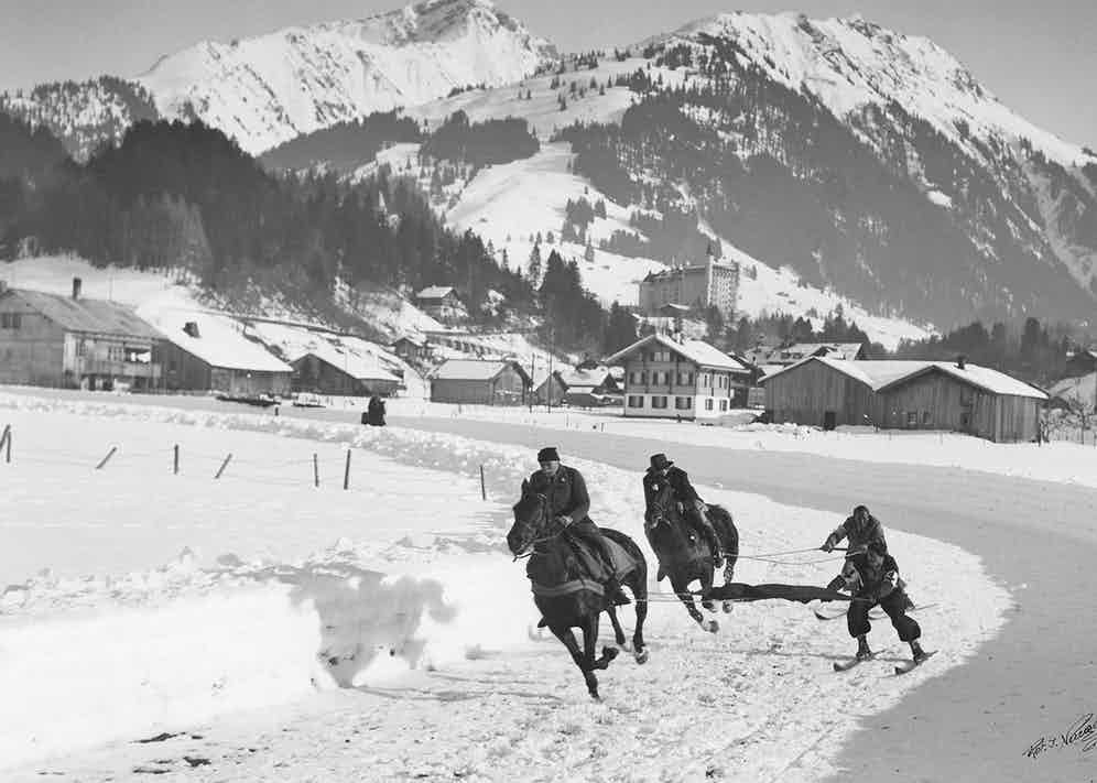 Horses pulling men on skis for local sport