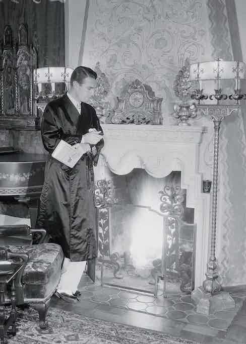 Randolf Scott leaning against fireplace (Photo by � Bettmann/CORBIS/Bettmann Archive/Getty)