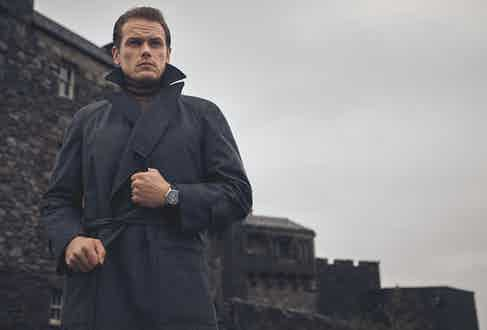 Storm-proof grey flannel raglan coat, Edward Sexton at The Rake; cashmere wool roll-neck, New & Lingwood; Code 11.59 by Audemars Piguet Selfwinding Chronograph,18-carat white-gold case, lacquered black dial and counters. Black alligator strap with white-gold buckle.