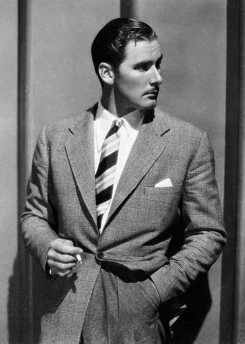 Errol Flynn wearing a jacket and tie and smoking a cigarette, 1936 (Photo via John Kobal Foundation/Getty Images)